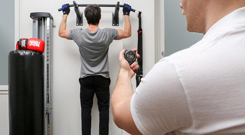 Esercizio in palestra, sotto lo sguardo di un personal trainer, per tonificare la forma fisica